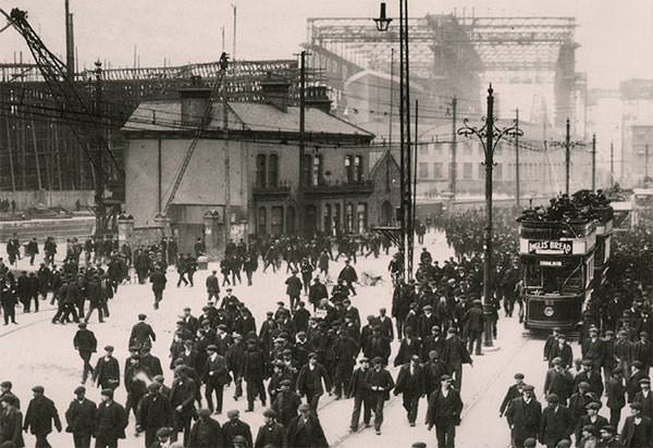 Workers heading home from the Harland and Wolff shipyard. In the background, beneath the Arrol Gantry, Titanic sits under construction.